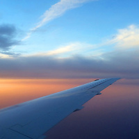 Airplane wing over midwest sunset skies.