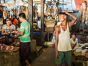 10 NOVEMBER 2014 - SITTWE, MYANMAR: A laborer waits for customers in the market in Sittwe. Sittwe is a small town in the Myanmar state of Rakhine, on the Bay of Bengal.    PHOTO BY JACK KURTZ
