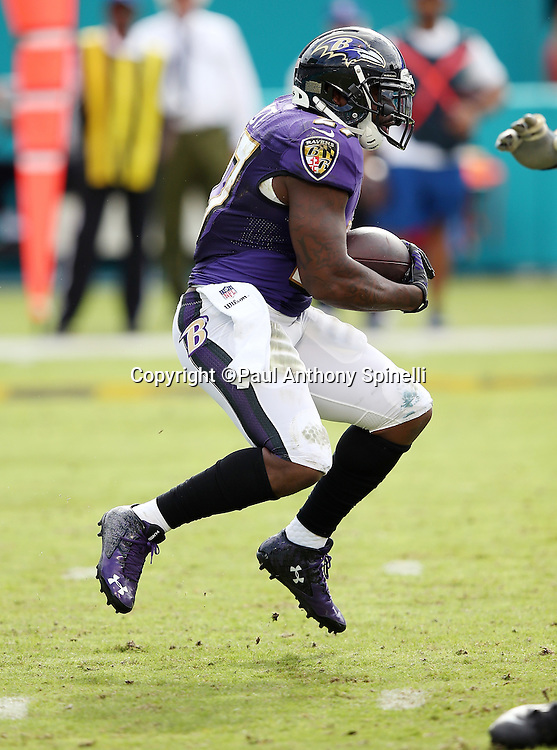 Baltimore Ravens running back Terrance West (27) gets some air as he runs the ball during the 2015 week 13 regular season NFL football game against the Miami Dolphins on Sunday, Dec. 6, 2015 in Miami Gardens, Fla. The Dolphins won the game 15-13. (©Paul Anthony Spinelli)