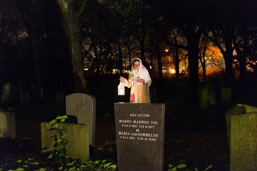 Nederland, Den Bosch, 20131102.<br /> Allerzielen op begraafplaats Orthen (Groenendaal) in Den Bosch.<br /> White Angels<br /> In het wit gekleed gaan zij langs de graven, stil en sereen. Hun windlicht schijnt over de woorden. Woorden van liefde, gemis en troost. U kunt ze zomaar treffen op uw pad. Laat u verrassen met een mooi gedicht door White Angels.<br /> Zielen in Gedachten is een jaarlijkse herdenkingsbijeenkomst voor iedereen die hun overledenen in een sfeervolle, ingetogen omgeving wil gedenken. Alleen of met anderen in gedachten stilstaan bij overledenen ongeacht waar deze begraven of gecremeerd zijn.<br /> Een sfeervol uitgelichte route voert langs o.a. muziek, rituelen, beelden, verhalen en po&euml;zie. In samenwerking met kunstenaars <br /> Netherlands, Den Bosch, 20,131,102. All Souls Day on cemetery Orthen (Groenendaal) in Den Bosch. Souls in Thoughts is an annual commemoration meeting for anyone who wants to remember their dead. In an attractive, understated surroundings Alone or with others in mind dwell on dead matter where they are buried or cremated. An attractively highlighted route goes past including music, rituals, images, stories and poetry. In collaboration with artists