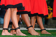 The feet of three hula girls dressed in red dresses.
