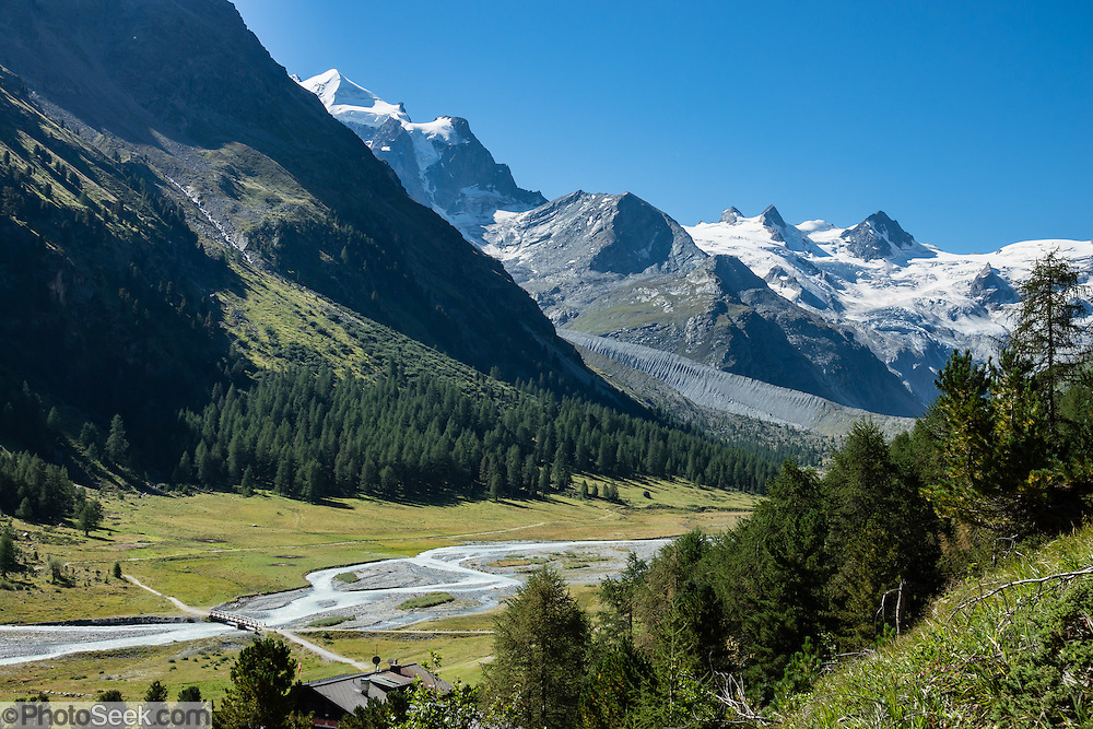 """The icy Bernina Range rises above Ova da Roseg river valley, near Pontresina, Switzerland, in the Bernina Alps, Europe. Tschierva Glacier flows from Piz Roseg (3937 m on left). At right (west), Roseg Glacier flows from Piz Glüschaint (3594 m). Val Roseg is in the Swiss canton of Graubünden (or Grisons / Grigioni / Grischun); the lower Roseg Valley is in Pontresina, whereas the upper valley is in an exclave of Samedan Municipality. Hike from Pontresina up Roseg Valley to Fuorcla Surlej for stunning views of Piz Bernina and Piz Roseg, finishing at Corvatsch Mittelstation Murtel cable car. Walking 14 km, we went up 1100 meters and down 150 m. Optionally shorten the hike to an easy 4 km via round trip lift. The Swiss valley of Engadine translates as the """"garden of the En (or Inn) River"""" (Engadin in German, Engiadina in Romansh, Engadina in Italian), and is part of the Danube basin."""