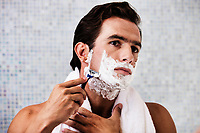 Portrait of young attractive man applying beard foam and shaving his beard while looking in the mirror
