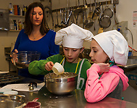 Karla Cooper watches as Charlotte Lehr and Alexandra Fay measure ingredients for their chocolate chip banana muffins during Gilford Youth Center's cooking class on Tuesday afternoon.  (Karen Bobotas/for the Laconia Daily Sun)