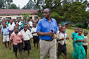 At Nyamiyaga primary school the head teachers leads the children to a health outreach program run by Bwindi Community Hospital.  As part of the outreach programme they cover 32 primary schools and 5 secondary schools in the region as well as many communities. The main Bwindi Community Hospital is in Buhoma village on the edge of the Bwindi Impenetrable Forest in Western Uganda. It serves around 250,000 people from the surrounding area.