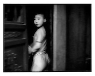 Suspicious glance from a young theatrical performer at the stage door.  Beijing, China.  2001
