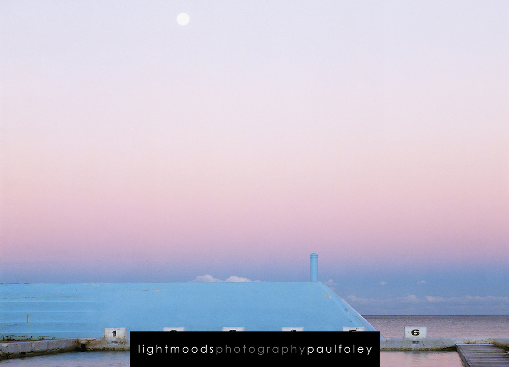 A swimmer rests between laps at Newcastle Ocean Baths as a full moon rises. Australia