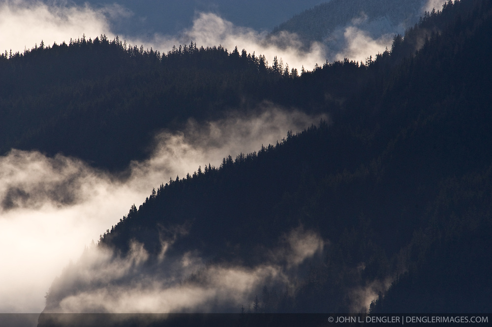 Morning fog lifts from the Takhin Ridge mountains near the Alaska Chilkat Bald Eagle Preserve near Haines, Alaska.