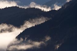 Morning fog lifts from the Takhin Ridge mountains near the Alaska Chilkat Bald Eagle Preserve near Haines, Alaska.