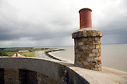 Coastal erosion, East Lane, Bawdsey, Suffolk, England view past chimney of martello tower