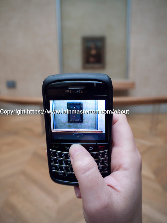 Detail of tourist photographing Mona Lisa painting with camera phone at The Louvre museum in Paris France