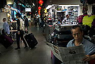 For a story by Dan Levin slug Hong Kong.February 19 2013, Kowloon, Hong Kong.In a commercial alley of the Chungking Mansions a shopkeeper reading a newspaper..Credit: Gilles Sabrie for The New York Times..
