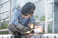 Man using arc welding equipment with protective gloves and visor.
