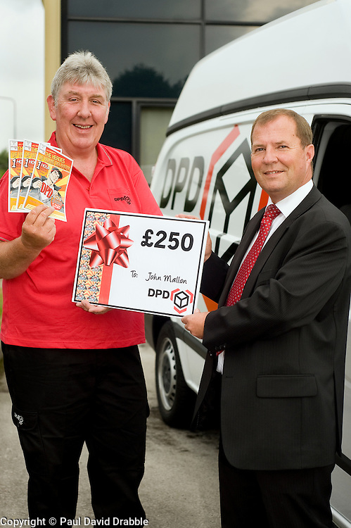 DPD Owner Driver Franchisee John Mallon (left) receives a gift voucher for £250 from Regional Manager Steve Church  at the DPD distribution centre  at Thorncliffe Chapeltown Sheffield 14  July 2010 .Images © Paul David Drabble.