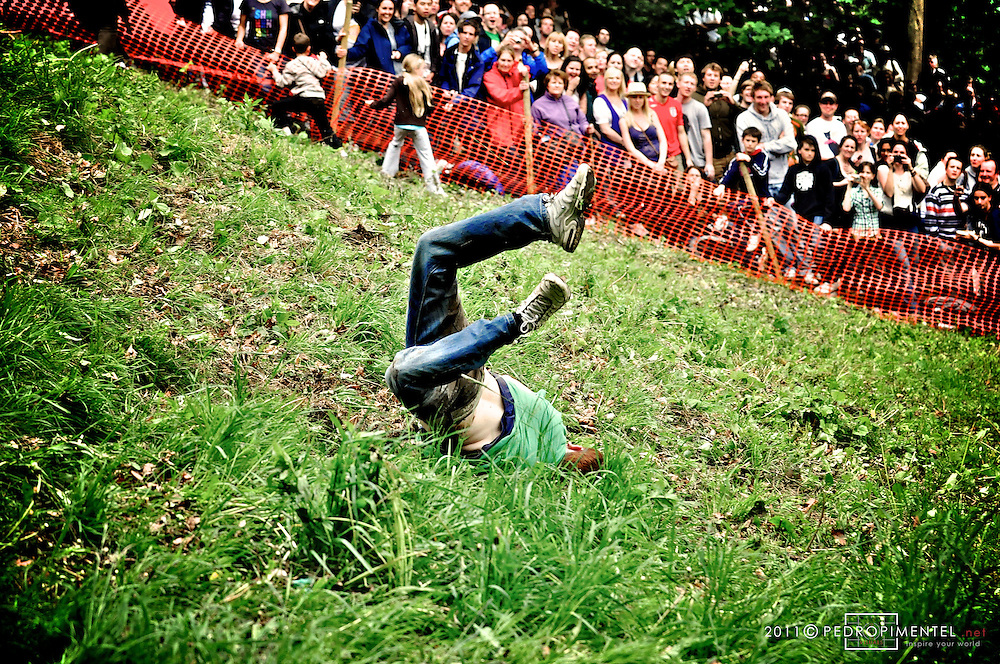 Cheese Rolling Festival. Competitor falling straight into his face after having been caught by the pull of gravity in a tragic way. Gloucestershire Cheese Rolling festival. Cooper's Hill, UK.