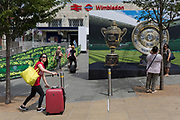 Passengers and pedestrians near a large hoarding showing the Mens' and Ladies' trophies, outside the Wimbledon railway station during the tennis championships, on 3rd July 2017, in Wimbledon, London, England.