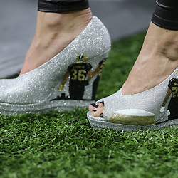 Jan 13, 2019; New Orleans, LA, USA; Ebbie Thomas (right) and son Niko Thomas (far left) wear special New Orleans Saints themed footwear before a NFC Divisional playoff football game between the Saints and the Philadelphia Eagles at Mercedes-Benz Superdome. Ebbie Thomas is the wife of Saints running backs coach Joel Thomas. Mandatory Credit: Derick E. Hingle-USA TODAY Sports
