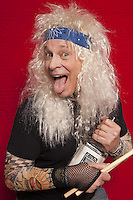 Portrait of senior musician holding drum stick and alcohol bottle while sticking out tongue