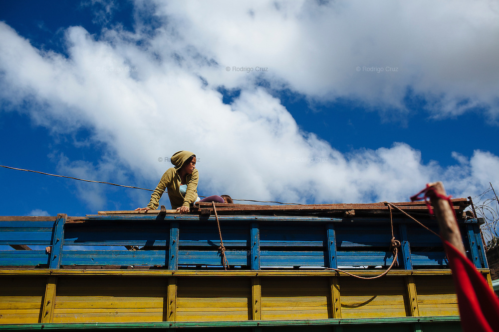 TEGUCIGALPA, HONDURAS - NOVEMBER 13, 2013: At the top of a bus a woman watches the arriving of supporters of Libre Party presidential candidate, Xiomara Castro, in Siguatepeque, Honduras. Castro, wife of ousted President Manuel Zelaya, is running for Honduran presidential elections on November 24. CREDIT: Rodrigo Cruz for The New York Times