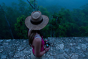 American tourist, Rachel Shockley, peers through the thick morning mist from atop of Temple IV at Tikal National Park, in the Petén Basin in Northern Guatemala.  Tourists gather to watch the silhouettes of Temple I, II and V appear as the mist clears.