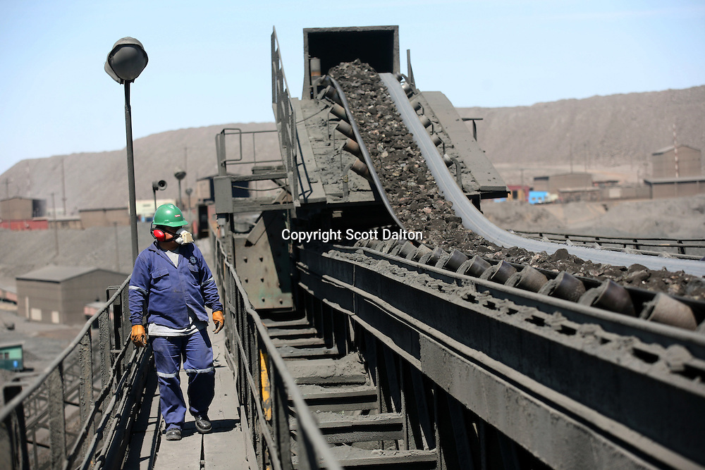 A worker keeps an eye on a conveyor belt at the iron mine of Shougang, a Chinese mining company, a Chinese owned and operated mine, just outside of Marcona, in southern Peru, on October 25, 2007. (Photo/Scott Dalton)