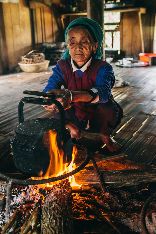 Grandmother tending the fire in kitchen of ethnic Tay house, Vietnam