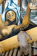 A worker sweeps the steps in front of the Mural Collectivo celebrating the culture of the indigenous Olmec people at the Palacio Municipal San Andres Tuxtla in San Andres Tuxtlas, Veracruz, Mexico. The well known mural was created by famous muralist Teodoro Cano Garcia and Carlos Chavez.