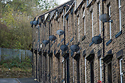 Satellite dishes on the walls of terraced houses in Skipton, North Yorkshire, UK.