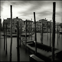The Grand Canal in Venice, Italy with mooring posts and boats looking across to buildings