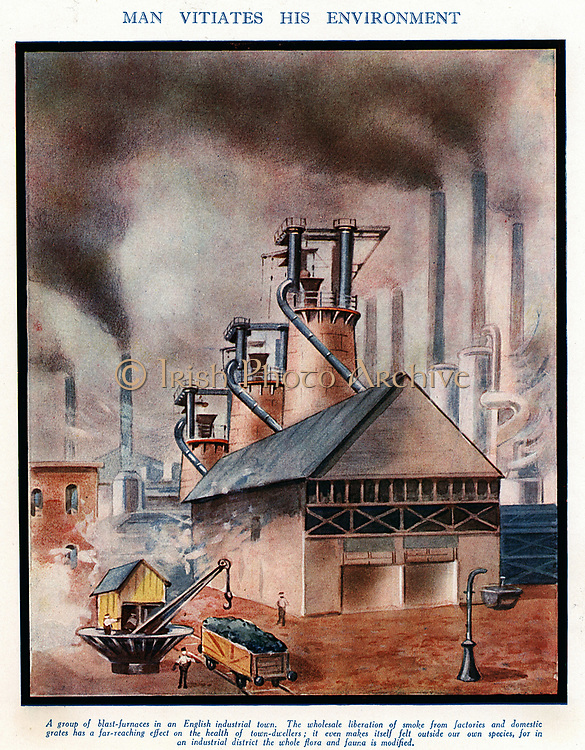 Group of typical early 20th century blast furnaces causing  with smoking chimneys causing atmospheric pollution.