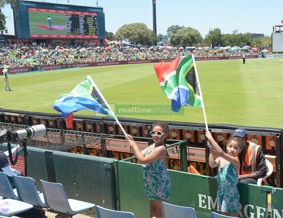 Pretoria 26-12-18. The 1st of three 5 day cricket Tests, South Africa vs Pakistan at SuperSport Park, Centurion. Day 1. Jaime(9) and her sister Jeanli Theys(6) from Primrose, Johannesburg waves  South African flags in the heat of the day as temperatures soared to around 35deg Celcius.<br /> Picture: Karen Sandison/African News Agency(ANA)