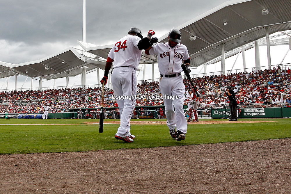 March 15, 2012; Fort Myers, FL, USA; Boston Red Sox second baseman Dustin Pedroia (15) celebrates with Boston Red Sox designated hitter David Ortiz (34) following a home run during the bottom of the fifth inning of a spring training game against the St. Louis Cardinals at Jet Blue Park. Mandatory Credit: Derick E. Hingle-US PRESSWIRE