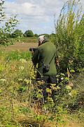 Person birdwatching at RSPB reserve, Boyton Marshes, Suffolk, England, UK