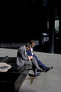 Dejected-looking businessmen sit looking at the ground in sunshine outside an office complex in the City of London.
