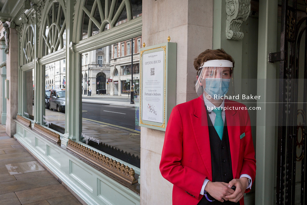 During the UK's Coronavirus pandemic lockdown and on the day when a further 255 deaths occurred, bringing the official covid deaths to 37,048, <br /> an employee Fortnum & Mason wearing a face mask and face shield stands outside the famous department store on Piccadilly, in preparation for the re-opening of their Food Hall on June 15th, as per governmental guidelines, on 26th May 2020, in London, England.