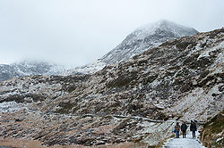 © Licensed to London News Pictures. 17/01/2018. Snowdonia National Park, Gwynedd, Wales, UK. Walkers on the Miner's Track beneath Mount Snowdon. Strong winds and hailstorms hit Snowdonia National Park last night. At the summit of Mount Snowdon the wind is forecast to be 50 mph with a feels-like temperature of minus 16 degrees centigrade. Photo credit: Graham M. Lawrence/LNP