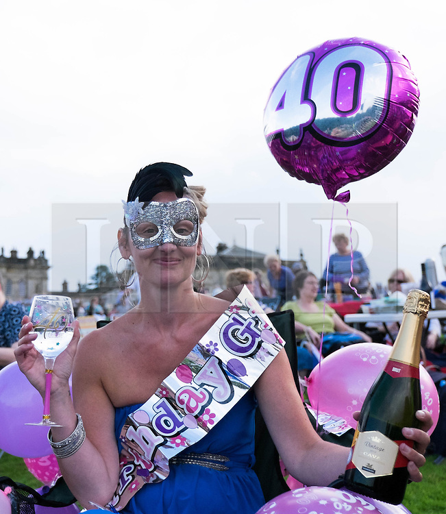 © Licensed to London News Pictures.22/08/15<br /> Castle Howard, North Yorkshire, UK. <br /> <br /> JOANNE MILLINGTON from Hull celebrates her birthday with friends as hundreds of people attend the 25th anniversary of the Castle Howard Proms event near York. The theme of the event this year is a commemoration of the 75th anniversary of the Battle of Britain and the 70th anniversary of VE day and brings an evening of classic musical favourites celebrating Britishness to the lawns of Castle Howard.<br /> <br /> Photo credit : Ian Forsyth/LNP