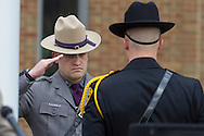 Goshen, New York - A New York State trooper, at left,  salutes during the Orange County Law Enforcement Officer Memorial Service in front of the county courthouse on May 2, 2014. The memorial service honors the memory of the 27 members of the Orange County law enforcement community that died in the line of duty. The service also pays tribute the families and loved ones left behind for their courage, dignity and perseverance.