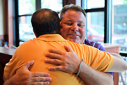 Mayor Peter Ursucheler and developer Manny DeMutis embrace upon meeting at Iron Hill Brewery in Phoenixville, PA, on August 21, 2018.