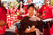 """10 OCTOBER 2010 - PHOENIX, AZ:  A boy dressed as a Spanish friar carries a doll representing Jesus in Phoenix, AZ, Sunday. About 500 people processed through downtown Phoenix Sunday afternoon to honor the Virgin of Guadalupe, the """"Queen of the Americas."""" The procession was accompanied by 12 Matachine dance troupes. The Matachines are an important part of Mexican Catholic culture. They represent the battle of Good vs. Evil and the protect the Virgin from malevolent forces, represented by the demon like figures who accompany the dancers.      Photo by Jack Kurtz"""