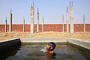 Arun Kashap, 8, is taking a bath in a pool of water used for building purposes in Jaibheem Nagar, pop. 10000, a large slum located near the banks of the Kali river (East), Meerut District, Uttar Pradesh, India, on Sunday, Mar. 16, 2008. Due to the heavy metal contamination of underground water sources, many of the residents are forced to walk 2-3 kilometres to reach a safer hand-pump, and those who are unable to do so, have to drink unsafe water which is the cause of many of the diseases affecting the local population.