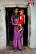 Sadma Khan, 19, poses with her 18 month old son for a portrait at the door of her shared house in her mother's house in a slum area of Tonk, Rajasthan, India, on 19th June 2012. She was married at 17 years old to Waseem Khan, also underaged at the time of their wedding. The couple have an 18 month old baby and Sadma is now 3 months pregnant with her 2nd child and plans to use contraceptives after this pregnancy. She lives with her mother since Waseem works in another district and she can't take care of her children on her own. Photo by Suzanne Lee for Save The Children UK