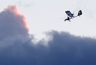 Pilot Rob Whiting comes in for a landing at Randall Airport in Middletown, N.Y., after towing a hang glider with his Dragonfly aero-tug ultralight aircraft on Friday, Aug. 23, 2013.  (AP Photo/Times Herald-Record/TOM BUSHEY)
