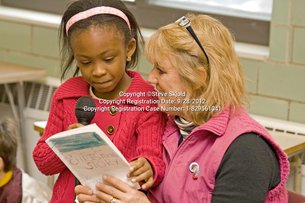 Teacher helping black female student age 5 read her classroom presentation. Expo Elementary School St Paul Minnesota MN USA