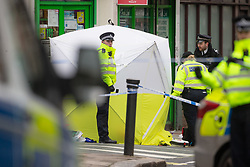 Police hold down the forensics tent as strong winds threaten to blow it away as it covers the body of a man in his 30s who was stabbed outside an off licence in the early hours of Sunday February 10th on Lordship Lane, East Dulwich in London. London, February 10 2019.
