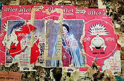 "DAN, NEPAL, APRIL 24, 2004:  Posters of the King and Queen of Nepal are covered by advertisements on a wall near Dan, in Western Nepal April 24, 2004. Support for the monarchy is low as Maoist guerrillas' fight for a ommunist state.Analysts and diplomats estimate there about 15,000-20,000 hard-core fighters, including many women, backed by 50,000 ""militia"".  In their remote strongholds, they collect taxes and have set up civil administrations, and ""people's courts"" to settle rows. They also raise money by taxing villagers and foreign trekkers. Though young, they are fearsome fighters and  specialise in night attacks and hit-and-run raids. They are tough in Nepal's rugged terrain, full of thick forests and deep ravines and the 150,000 government soldiers are not enough to combat this growing movement that models itself after the Shining Path of Peru. (Ami Vitale/Getty Images)"