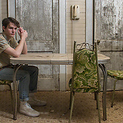 A Caucasian teenaged boy holds a 45 record with others scattered around his feet. The same Caucasian 17-year-old sits at a kitchen table and in a barcalounger next to a Christmas tree in the upstairs bedroom of an old farm house.