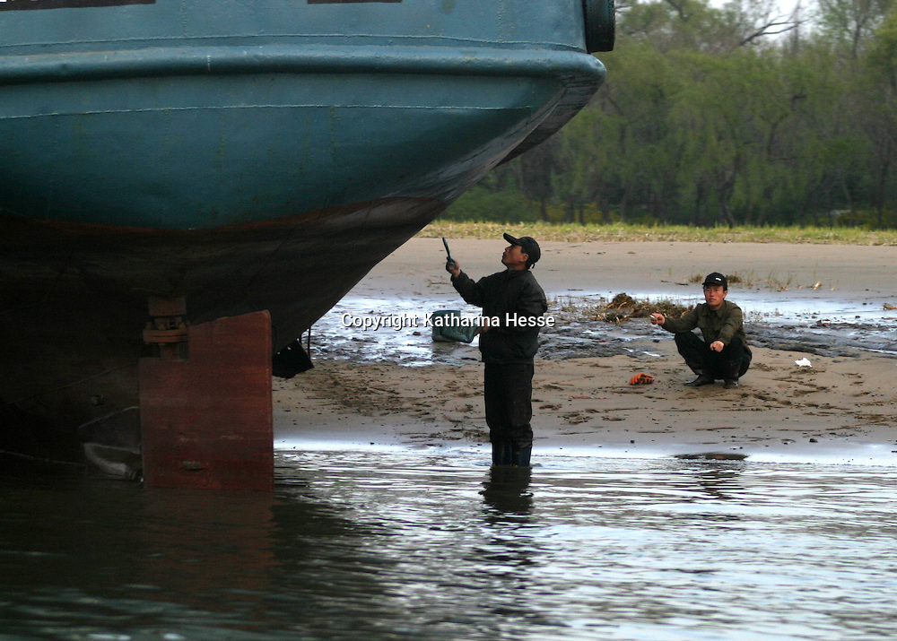 SINUIJU, NORTH KOREA - APRIL 24: A North Korean worker paints a boat in Shiniuju harbour across the border from Dandong, China on April 22, 2004 in Sinuiju, North Korea. At least 154 people died and more than 1300 were injured following a train explosion in Ryonchon, a North Korean town 20 km from the Dandong border. China has vowed to give North Korea $1.21 million worth of medical supplies, tents and food to help it cope with the disaster.