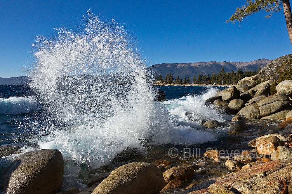 An image of a curling splash on the Nevada shore of Lake Tahoe. I've walked the Nevada shore of the lake for years during high-wind days looking for the perfect splash spot. A number of factors have to be just right; the depth of the water leading up to the rock, a lack of obstructions in front of the chosen rock and the shape of the rock the wave runs in to. This spot meets all three requirements. The rock is actually undercut so it sends the splash curling backwards.