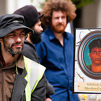 London, UK - 15 June 2012: a protester next to a banner remembering the death of Abhilash Jhodia during the Carnival of Dirt. Abhilash Jhodia was killed in 2000 during a protest against a proposed bauxite mine and refinery in Orissa.